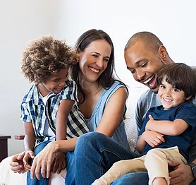 happy family sitting together on a couch, laughing and smiling